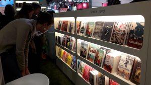Messeregal mit den Graphic Novels von Carlsen, davor zwei Besucher, die es betrachten