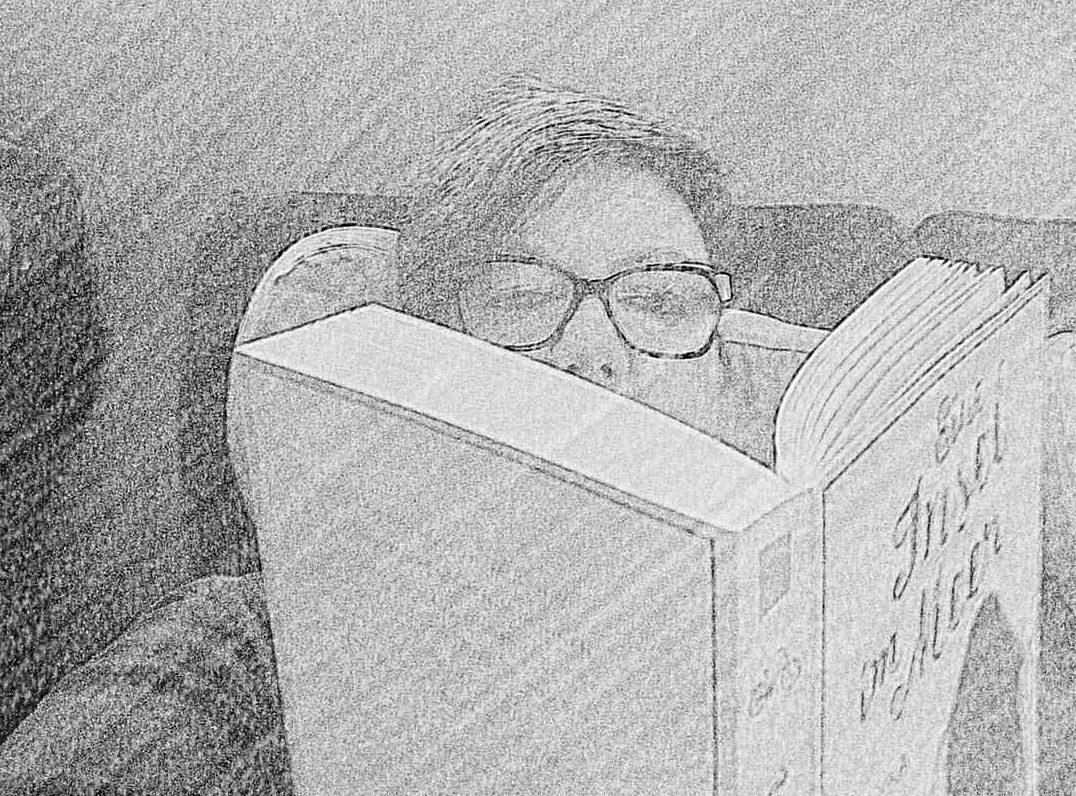 Frau mit Brille liest im Zug in einem Buch