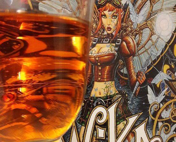 Weinglas mit orangefarbener Flüssigkeit im Vordergrund vor Cover des Comics Wika Band 2, das eine Fee zeigt