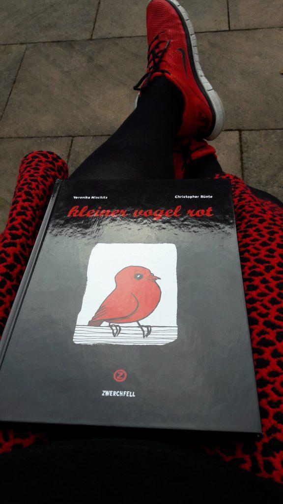 Schwarzer Comic mit einem roten Vogel in der Mitte