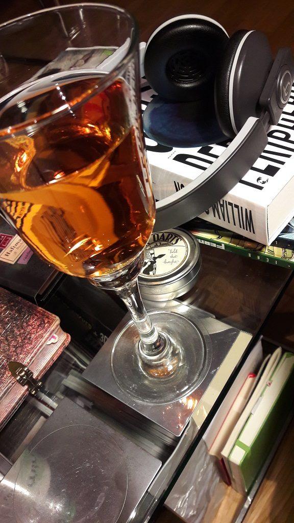 Glas mit orangefarbener Flüssigkeit im Vordergrund, dahinter das Buch und darauf ein Kopfhörer