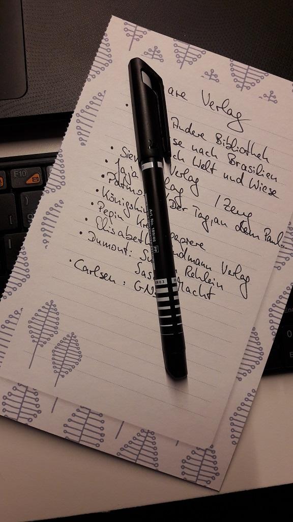 Liste in schwarz geschrieben auf Papier, darauf ein schwarzer Stift