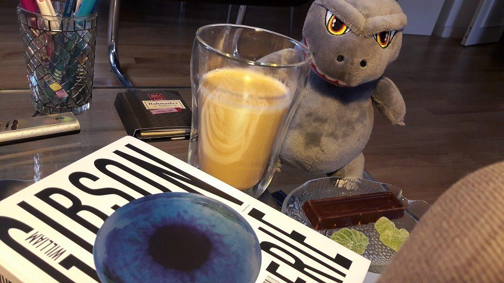 Buch im Vordergrund, dahinter ein Kaffee im Glas und ein Plüsch-Godzilla