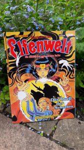 Comic Abenteuer in der Elfenwelt 37 von Bastei vor einer blühen Pflanze, auf dem Cover sind zwei Elfen