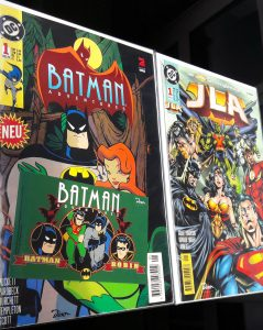 Links Batman Adventures Heft 1 mit Batman und Poison Ivy, rechts JLA 1
