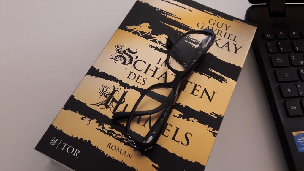 Buch mit goldschwarzem Cover auf dem eine schwarze Brille liegt