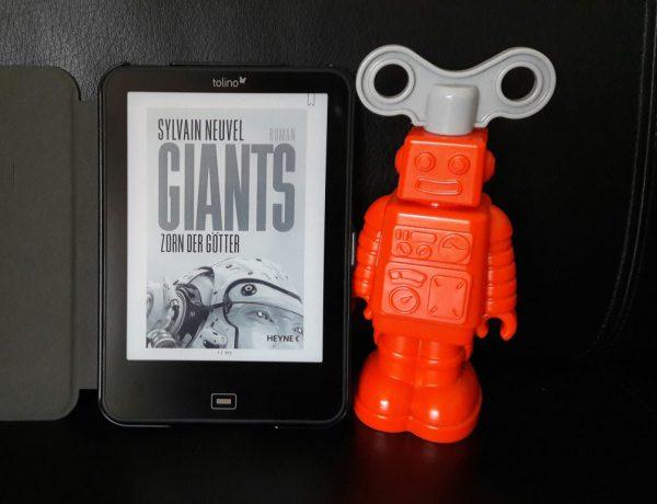 """E-Book """"Giants. Zorn der Götter"""" steht auf einem schwarzen Hintergrund, rechts daneben ein orangefarbener Kunststoffroboter"""