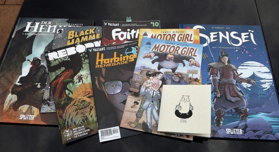 9 Comics liegend auf einem Glastisch