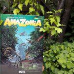 Comic inmitten von Pflanzen. Auf dem Cover eine Dschungellandschaft, eine Frau durchquert sie auf einem Boot