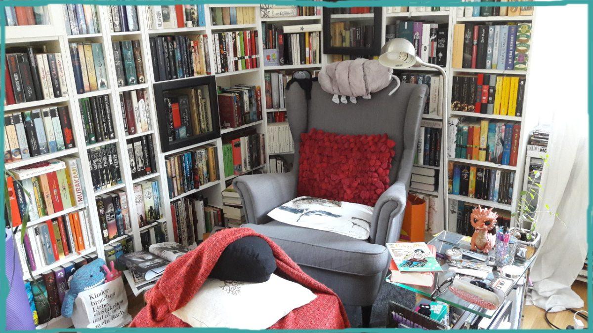 Bild einer Leseecke mit grauem Ohrensessel, Kissen, Decke und runherum weiße gefüllte Bücherregale