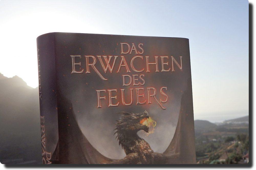 Buchcover vor einer Berglandschaft. Cover zeigt einen feuerspeienden Drachen.
