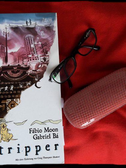 Cover des Comics, daneben eine schwarze Lesebrille und ein Brillenetui in rot mit weißen Punkten. Alles auf rotem Hintergrund