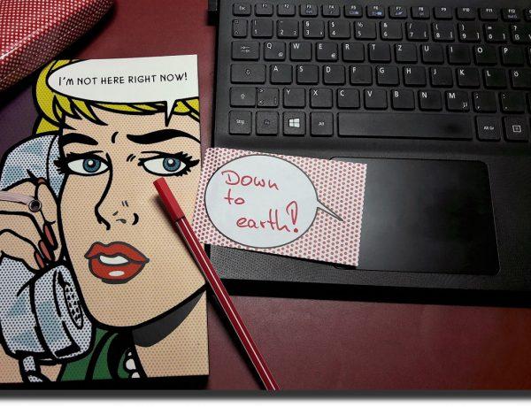 """Frau in Comic-Style auf einem Notizbuch, ein roter Stift, ein Klebezettel mit Aufschrift """"Down to earth!"""" und ein Notebook"""