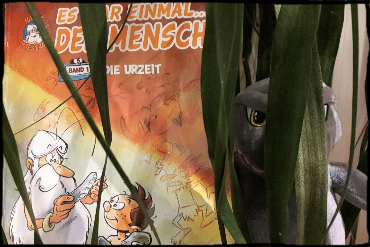 Comic versteckt sich hinter einer Pflanze und rechts lukt ein Plüsch-Godzilla durch die Blätter