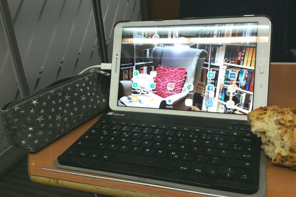 Tablet mit Tastatur, daneben eine Faulenzermappe und ein Brötchen im Zug