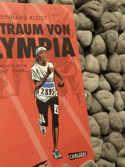Comicband vor einem grauen Hintergrund. Cover zeigt Läuferin vor rotem Hintergrund (Laufbahn) und bewaffneten Männern