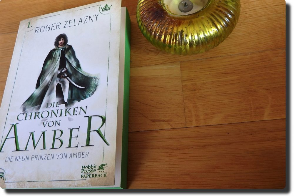 Buch liegt neben einem grünen Teelichthalter auf einem Holzboden