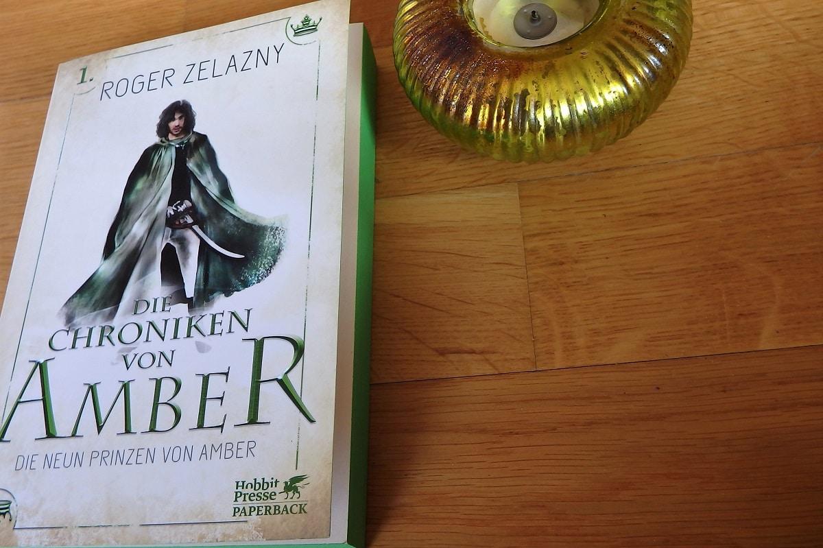 Buch mit grünem Buchschnitt neben einem Kerzenhalter in grün auf hölzernem Untergrund