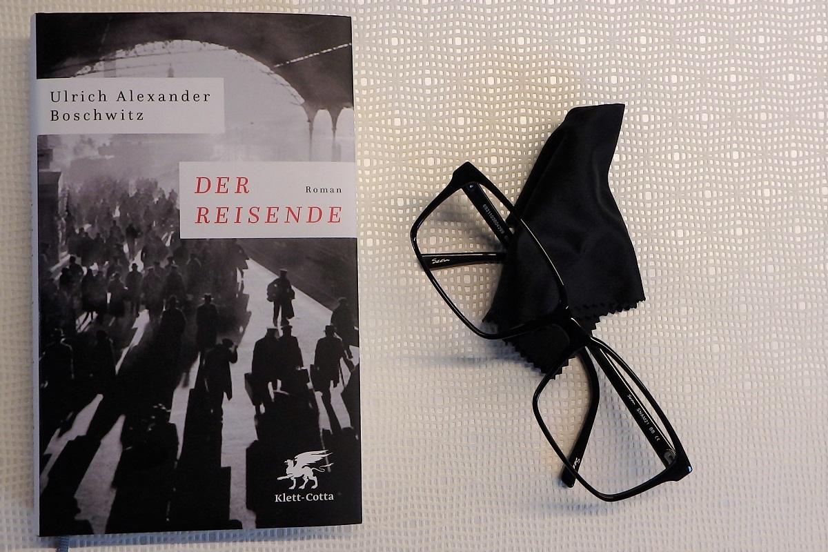 Buch liegt neben einer schwarzen Brille und einem Tuch auf einem hellen Untergrund