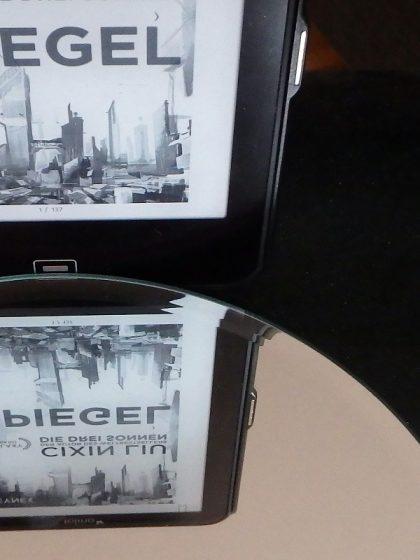 E-Book-Reader auf dem das Buchcover zu sehen ist, welches sich wiederum in einem Spiegel spiegelt