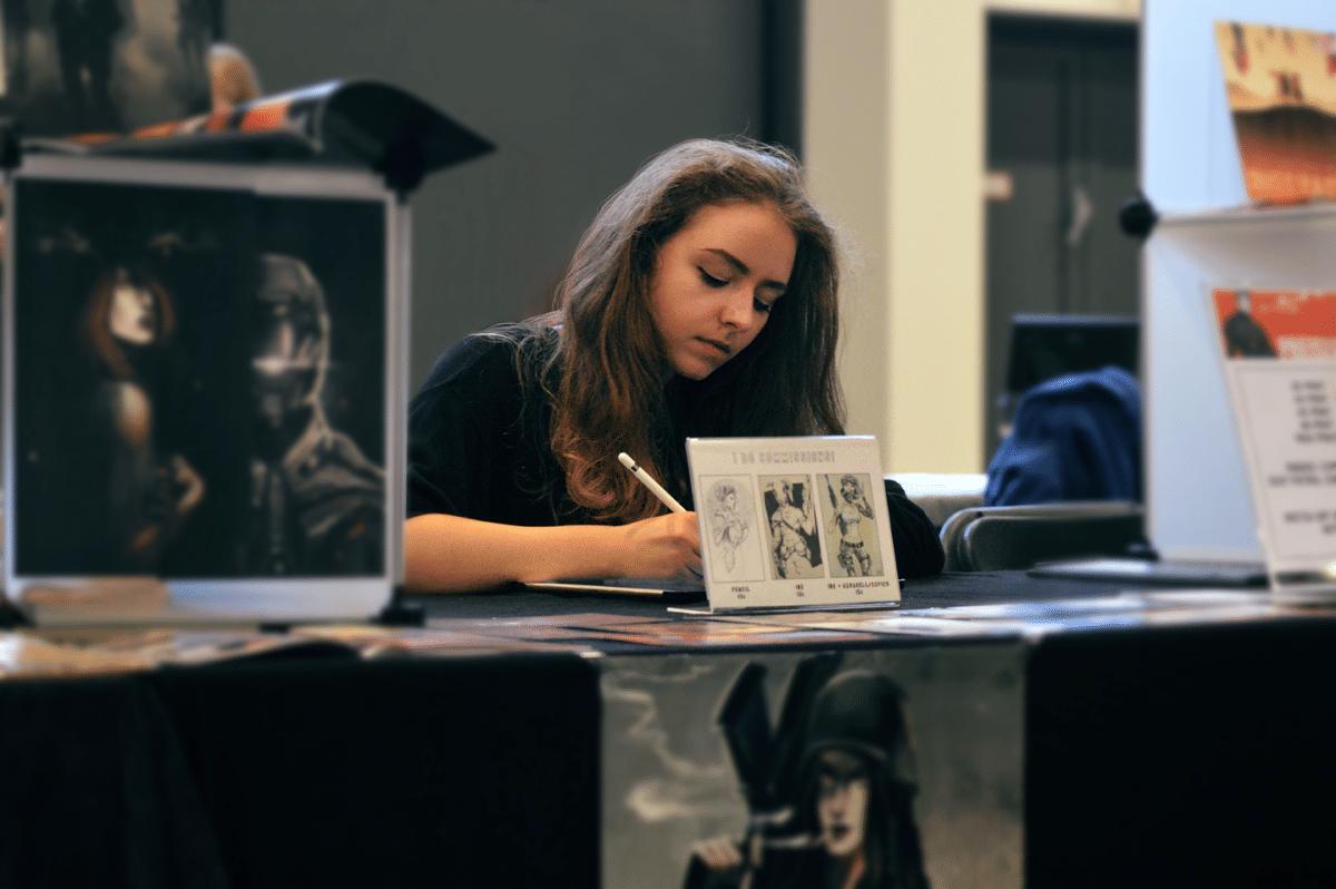 Junge Frau sitzt an einem Tisch inmitten ihrer Zeichnungen und arbeitet konzentriert