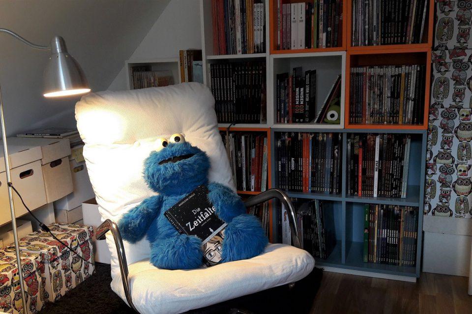 Titelbild zeigt einen weißen Sessel mit Chrom auf dem ein Krümelmonster sitzt, dahinter ein Regal mit Comics