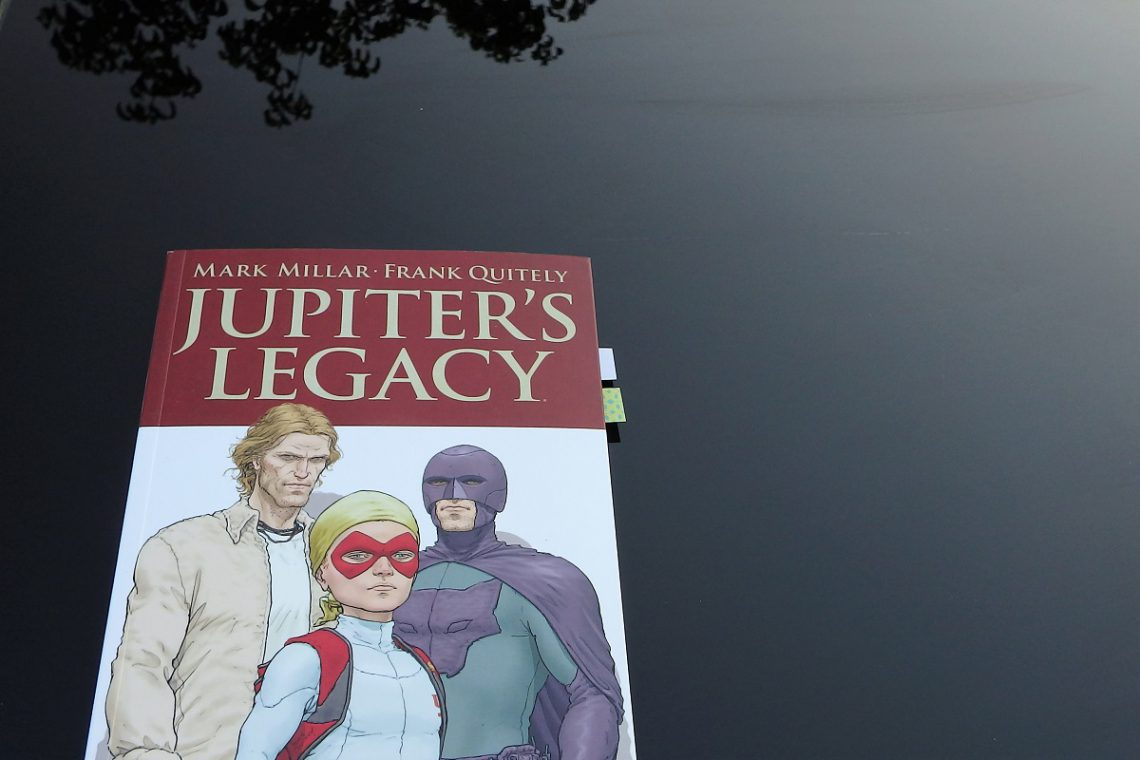 Comic auf einem spiegelnden Glastisch, der schwarz wirkt. Superheldenfamilie auf dem Cover