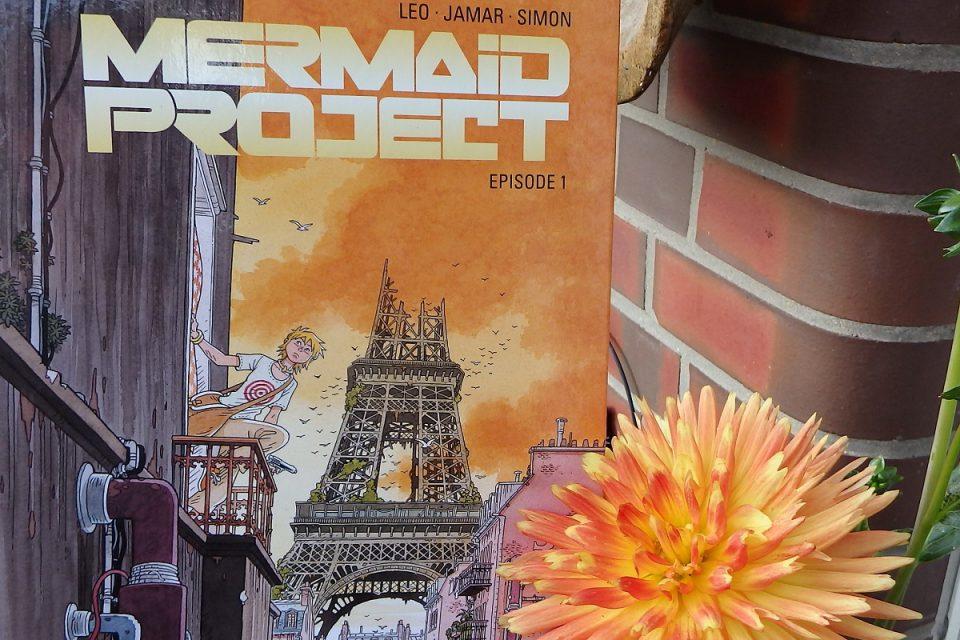 Mermaid Project Titel neben einer großen orangefarbenen Dahlienblüte