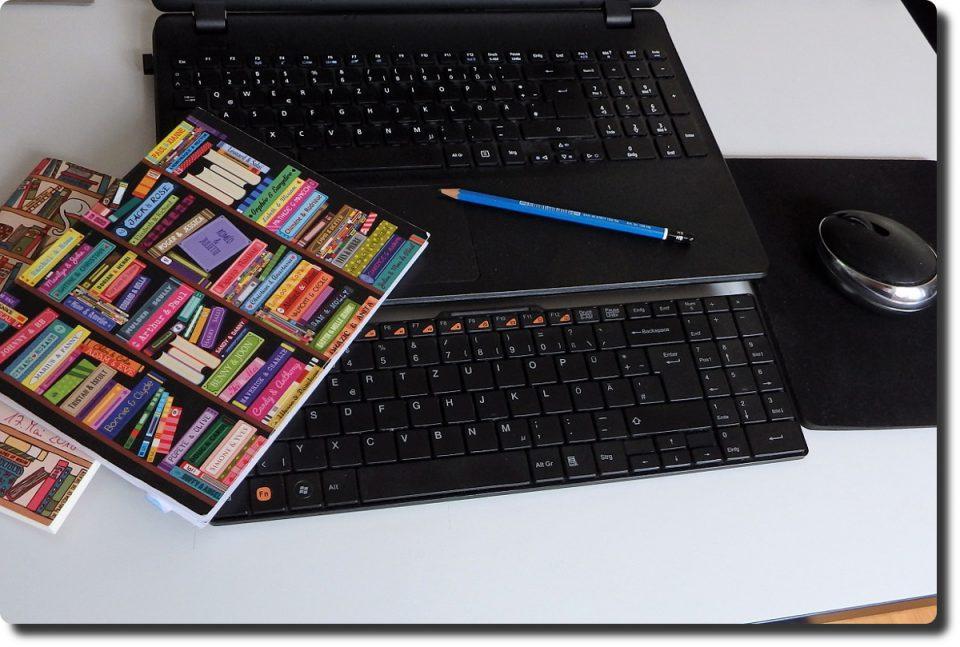 Zeigt eine Tastatur, einen Bleistift und ein Notizbuch