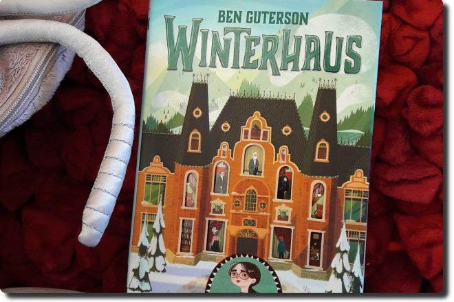 Winterhaus Cover - Buch liegt auf einem Kissen. Auf dem Cover ist das altmodische Hotel mit Einblick in viele Fenster