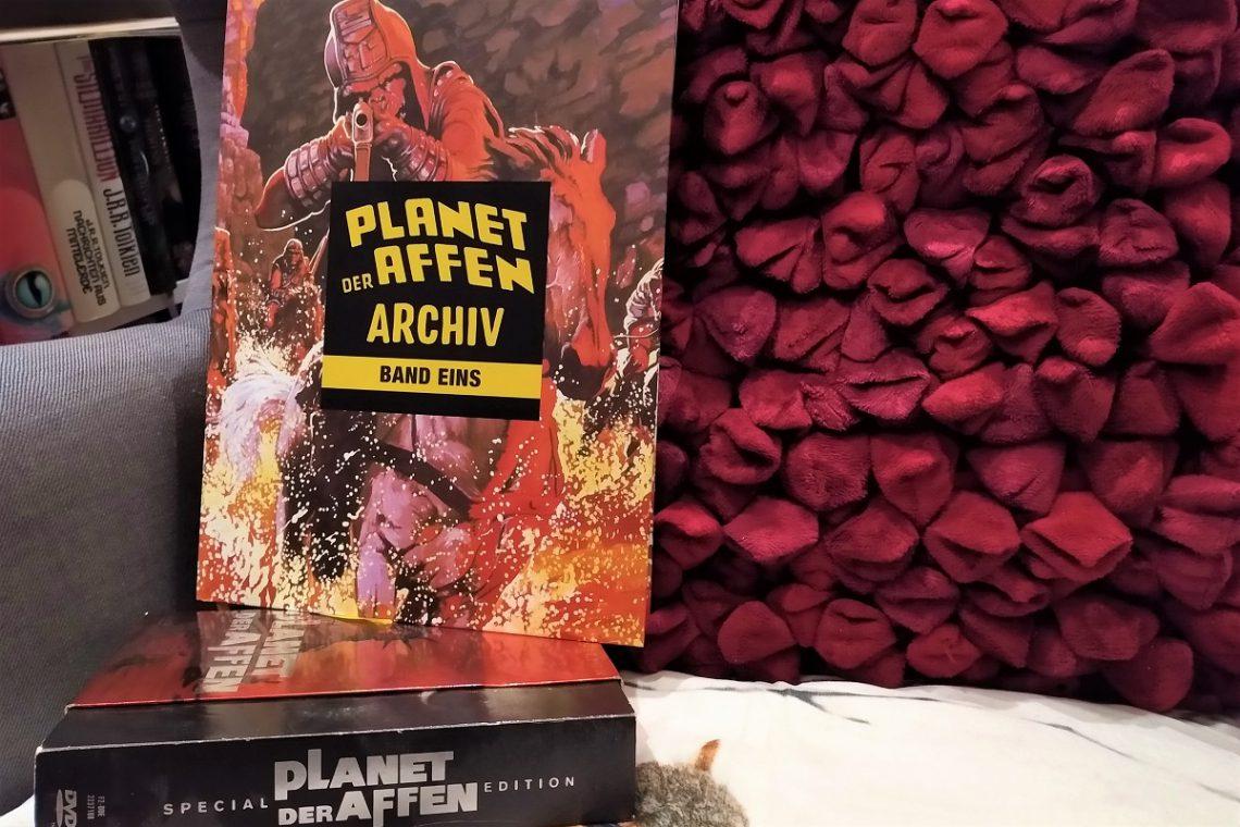 Planet der Affen Archiv 1 Titelbild zeigt den Comic auf einem Sessel vor einem roten Kissen und auf der Planet der Affen-DVD-Box