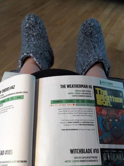 Aufgeschlagener Katalog auf den Beinen und an den Füßen plüschige Hausschuhe