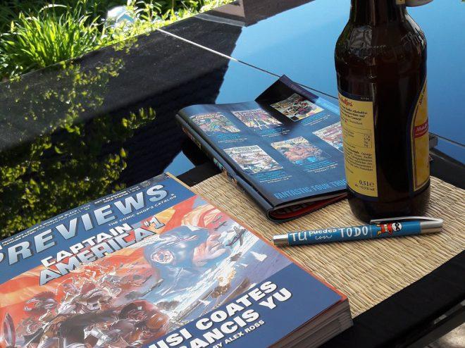 Previews Katalog, daneben die Marvel-Vorschau und eine Flasche Bier im Garten