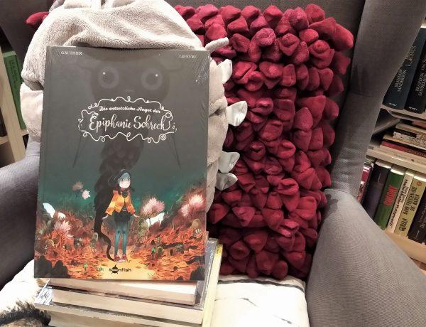 Epiphanie - Comic steht auf einem Bücherstapel auf einem Sessel