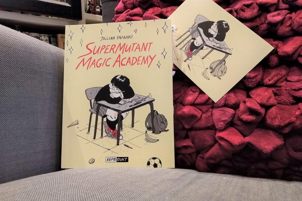 Comic vor einem roten Kissen, daneben eine Postkarte mit dem Comiccover