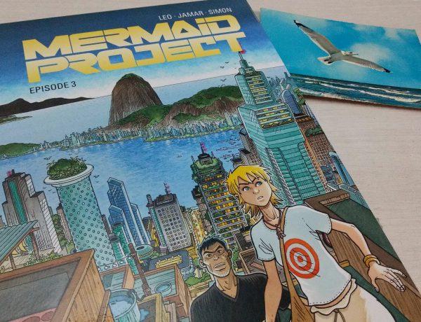 Mermaid Project 3 - der Comic liegt neben einer alten Postkarte mit einer Möwe über dem Meer