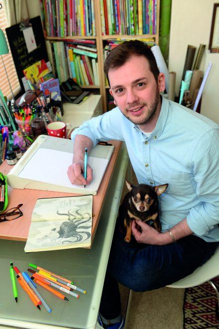 Autor sitzt an einem Schreibtisch, schaut in die Kamera und hat Zeichnungen vor sich.