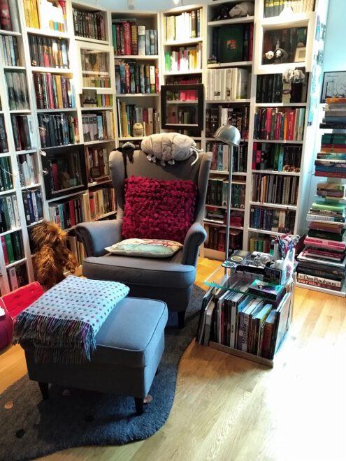 Ecke mit Bücherregalen und einem grauen Lesesessel mit Hocker und Tischchen