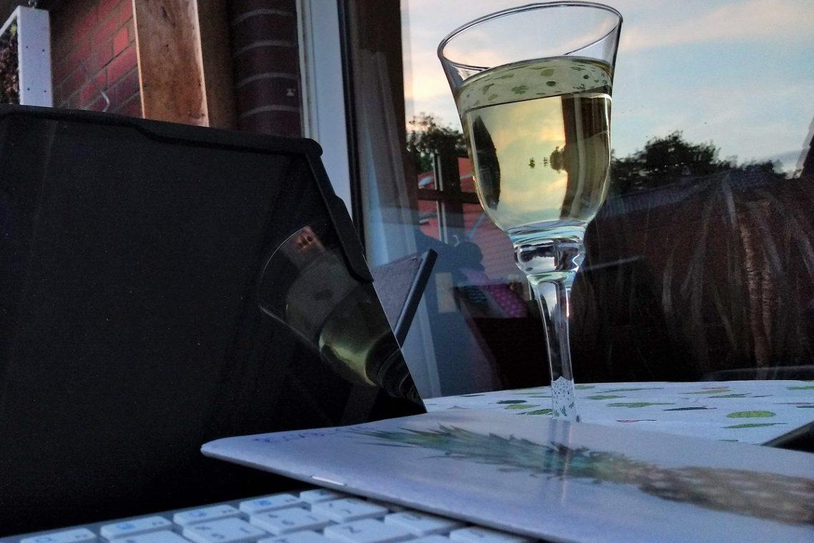Notebook und ein Glas Weißwein