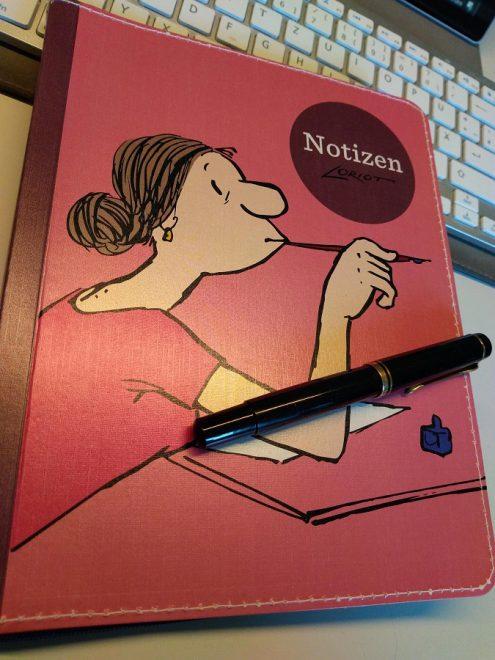 Notizbuch mit einer Illustration von Loriot auf dem Cover und darauf liegt ein Füller