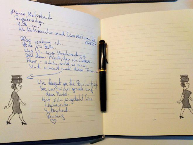 Offenes Notizbuch mit Text in Handschrift, schwarzgoldener Füller liegt im Buch