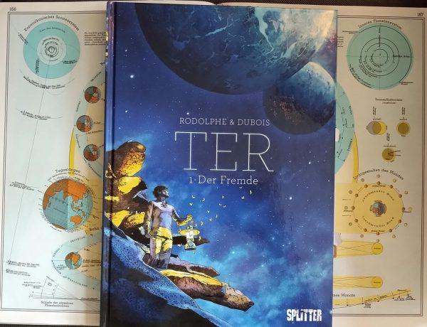 Comic liegt auf einem aufgeschlagenen Atlas, der Planeten zeigt