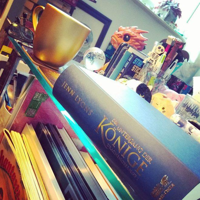Buch und Kaffeetasse und überall Bücher