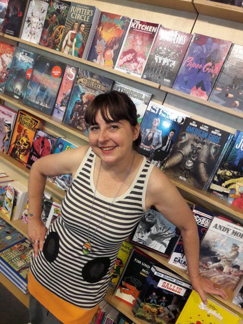 Frau in einem gestreiften Kleid vor einem Regal mit Comics