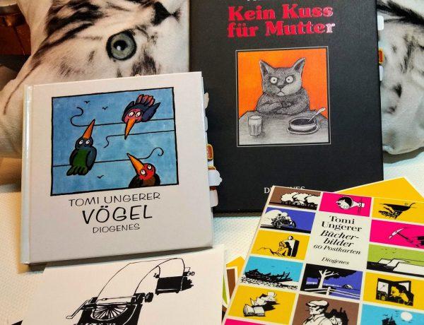 Alle drei Titel auf einem Bild, im Hintergrund ein Kissen mit Katzenaufdruck