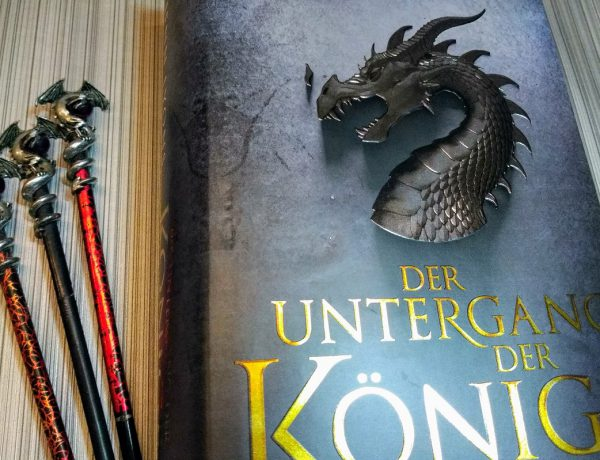 Buch neben drei Stäben an denen oben silberne Drachen befestigt sind