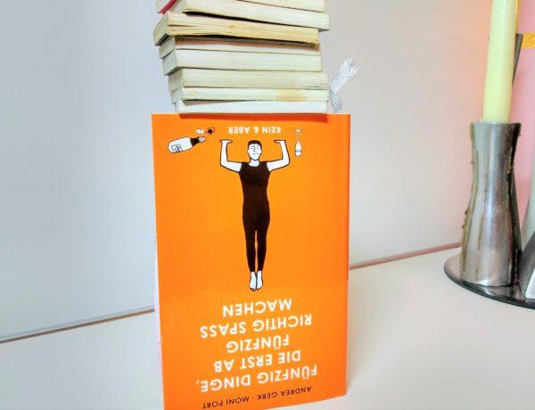 Orangefarbenes Buch steht auf dem Kopf und obendrauf liegen kleine Minibücher mit dem Buchschnitt davor. Auf dem Cover eine Frau, die diese kleinen Bücher zu tragen scheint
