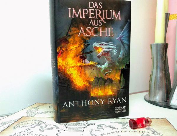Buch mit feuerspeiendem Drachen auf dem Cover vor weißem Hintergrund, darunter eine Karte, daneben Kerzen