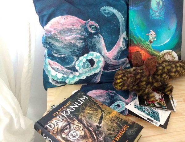 Ein Kissen mit Oktupus darauf, daneben ein Comic, davor Postkarten und ein Jugendroman