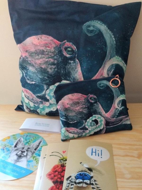 Kissen und Täschchen mit Krakenmotiv, davor Postkarten mit Insektenzeichnungen